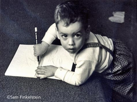 Little boy looks up from his drawing